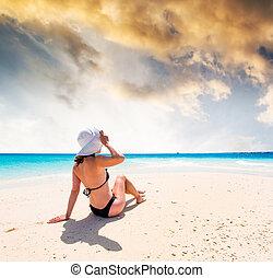 girl in hat sitting on beautiful beach