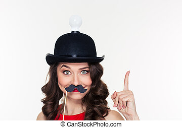 Girl in hat with light bulb using fake moustache props