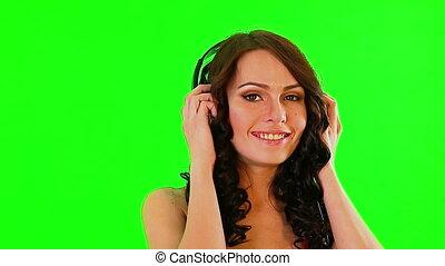 Girl in headphone listen music. Green screen. - Girl wearing...