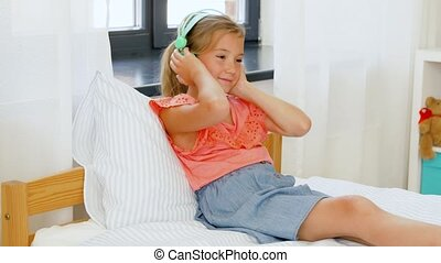 girl in headphones listening to music on cellphone -...