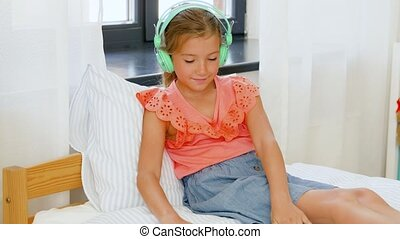 girl in headphones listening to music on tablet pc -...