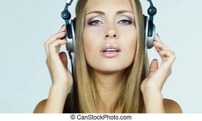 Girl in headphones listens, asks, laughing