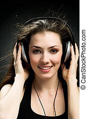 girl in headphones on the black background