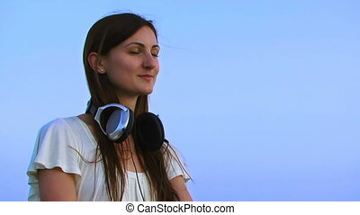 Girl in headphones on the skyline