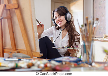 girl in headphones paints with oil colors on canvas