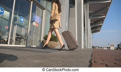 Girl in heels walking to airport and rolling suitcase on wheels. Business lady entering going to glass door with her luggage. Woman carrying a suit case. Trip or vacation travel concept. Slow motion