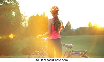 Girl in helmet on bicycle in park with city horizon - Girl...