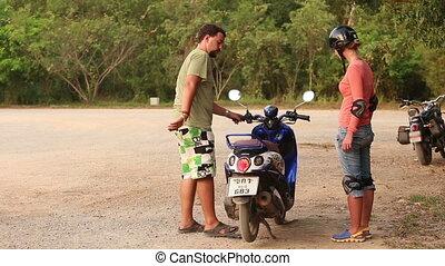 girl in helmet sits down on running scooter - girl in motor...