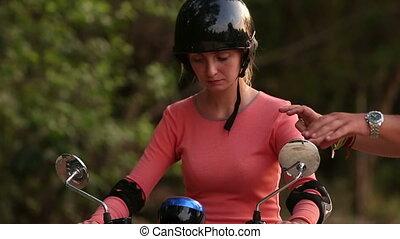 girl in helmet starts driving scooter