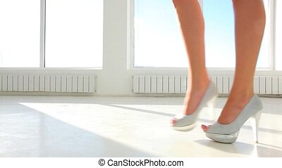 Girl in high heels walking against panoramic sunny window. Dolly shot clip