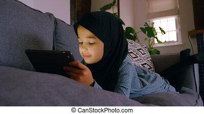 Girl in hijab using digital tablet in living room 4k - Girl...