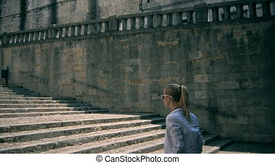 Girl in historical center of Girona go up. Tourist model, a lot of stairs.