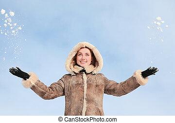Girl in hood throws hands snow upwards