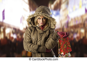 attractive blond woman with shopping bag covering her head with hood from winter