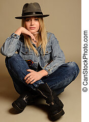 Girl in jeans, boots, hat and jacket sitting