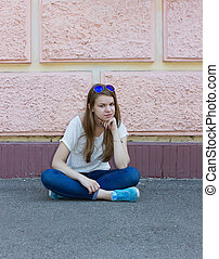 girl in jeans sitting on ground