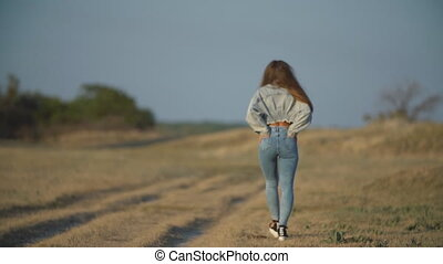girl in jeans walks along the road - girl in jeans walks...