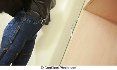 girl in jeans with leather garter new fashion trends. straps on the hips. leather belts