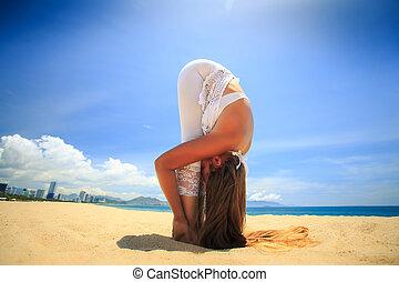 girl in lace in yoga asana standing forward bend on beach