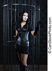 Girl in leather suit is large cage dark room. She looks like...