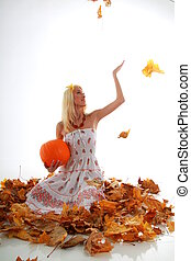 Girl in leaves with pumpkin