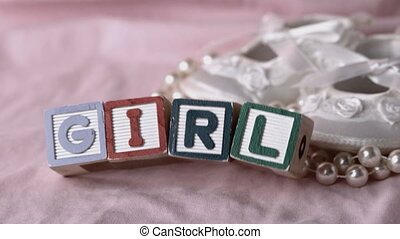 Girl in letter blocks beside booties and pearls on pink...
