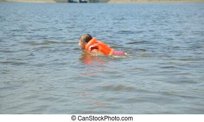 Girl in life jacket in water