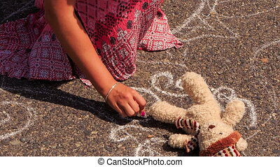 Girl in Long Draws with Chalk on Pavement around Toy Bear