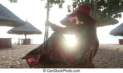 girl in long dress swings on beach near umbrellas