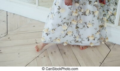 girl in long dress with flowers turns dancing