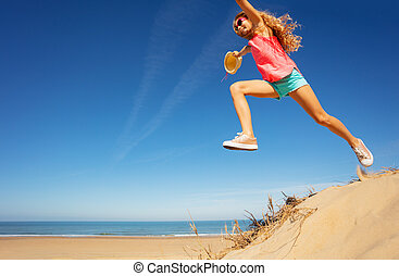 Girl in long jump from sand dune on the sea beach