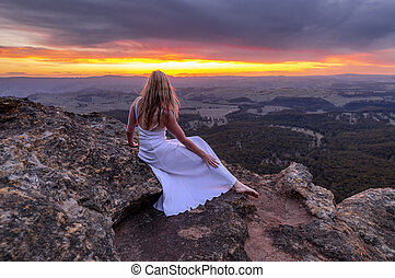Girl in long white dress watching the sunset at Mt Blackheath