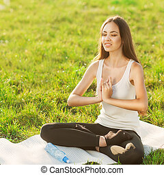 girl in lotus pose at sunset