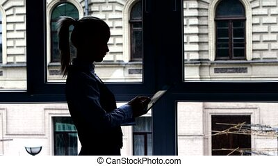 Girl in  lunch break reading book on your tablet standing at the window. Silhouette