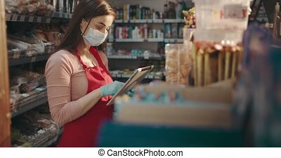 Girl in mask and gloves doing revision with tablet at store...