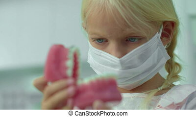 Small girl in mask is looking at medical jawbone.