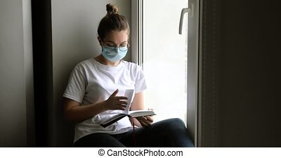 Girl in mask reads book studying sits on windowsill on ...