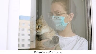 Girl in mask and glasses with cat is missing about usual normal life on quarantine at home looking at window. Depression in self-isolationg during covid-10 pandemic, epidemic. Portrait of woman.