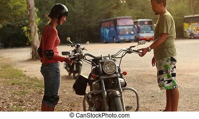 girl in motor helmet try to keep balance of motorbike
