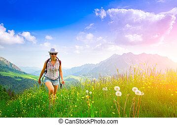 Girl in mountain meadow blowing flower