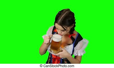 Girl in national Bavarian costume drinking a beer. Green...
