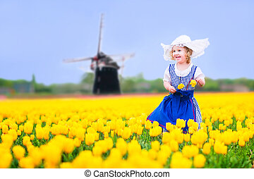 Girl in national costume in tulips - Adorable curly toddler ...