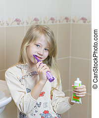 Girl in nightgown with an electric toothbrush in the bathroom.