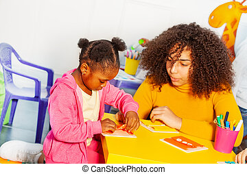 Girl in nursery school learning to button unbutton