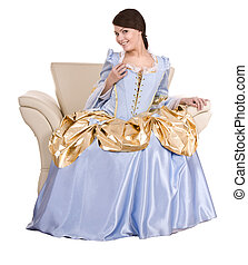 Girl in old long blue with gold dress on armchair. Isolated....