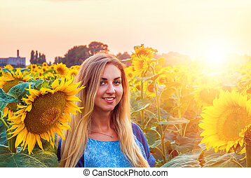 girl in on a field of sunflowers during the sunset