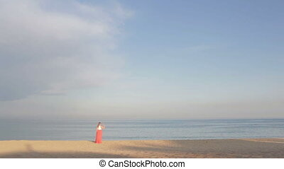 Girl in orange dress says good bye to the sea and walking...