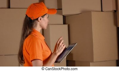 Girl in orange uniform counting storage boxes and using her tablet against brown cartons backround. Modern business technologies. 4K video