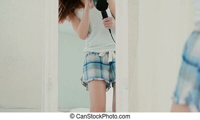 Girl in pajamas dancing near the mirror. Woman looks at the reflection and sings, using hair as microphone. Slow motion.