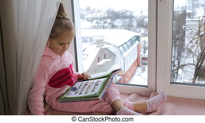 Girl in pajamas reading a book sitting on the windowsill